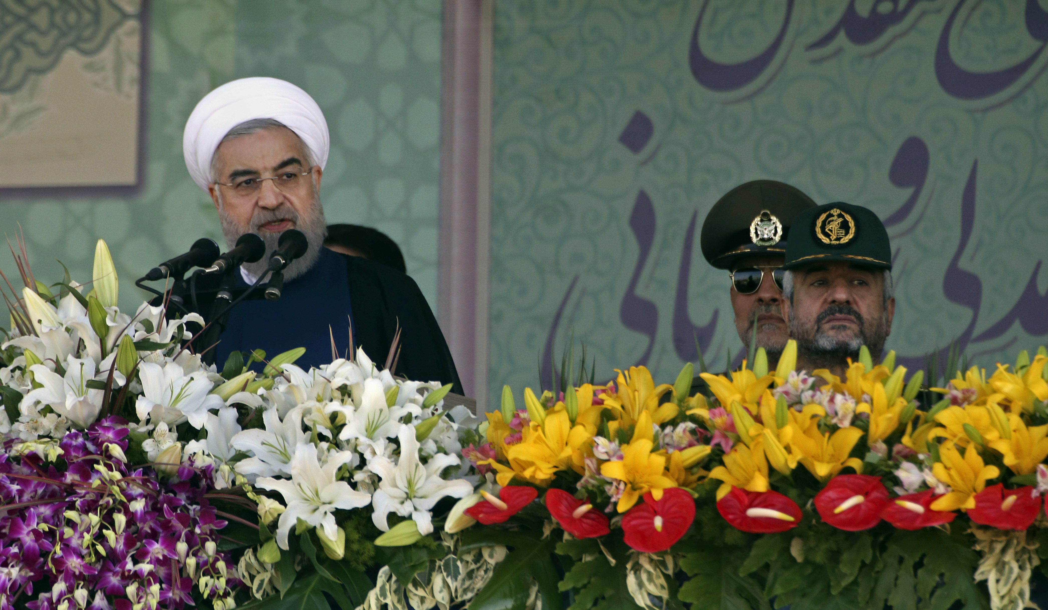 Iranian President Hassan Rouhani, left, speaks at a military parade marking the 35th anniversary of Iraq's 1980 invasion of Iran, attended by Revolutionary Guard commander Mohammad Ali Jafari, right,in front of the shrine of the late revolutionary founder, Ayatollah Khomeini, just outside Tehran, Iran, Tuesday, Sept. 22, 2015. President Rouhani said Tuesday his countryu0092s military is the most reliable force to take on u0093terrorists in the regionu0094 - a reference to the extremist Islamic State group. (AP Photo/Vahid Salemi)