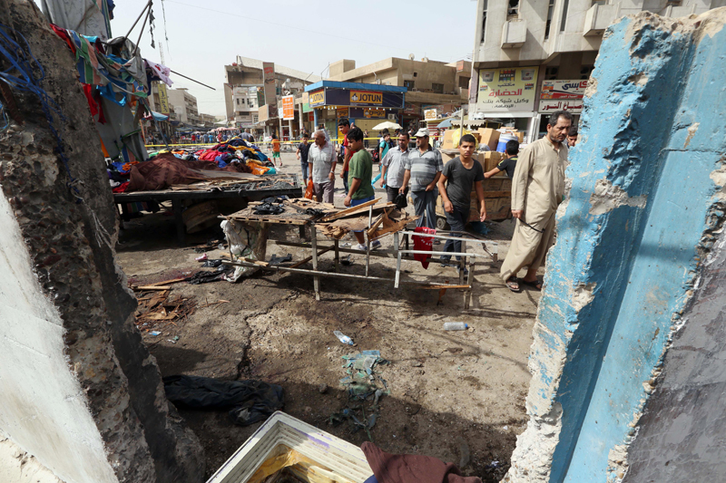 Civilians inspect the aftermath of a suicide bomb attack in Baghdad, Iraq, Thursday, Sept. 17, 2015. Iraqi officials say two suicide attacks have targeted police checkpoints in commercial areas in central Baghdad. Photo: AP