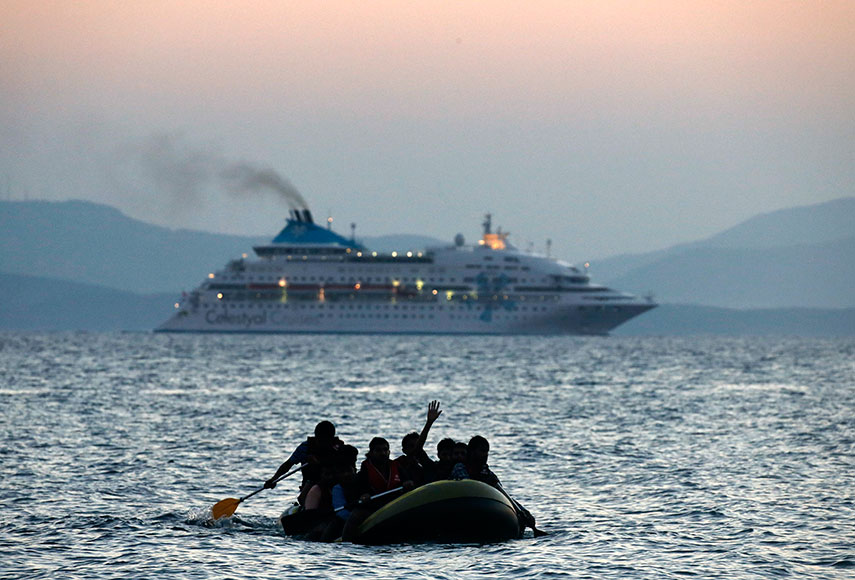 Migrants from Pakistan wave to a cruise ship as they cross the Aegean, August 2015. Photo: Reuters