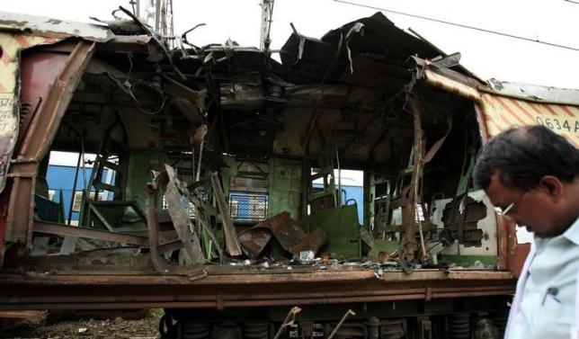 A forensic officer examines a damaged railway train compartment hit by bomb blast in Mumbai July 12, 2006. REUTERS/Punit Paranjpe/Files