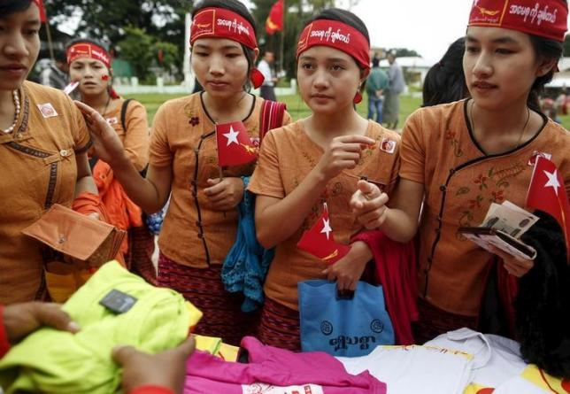 Ethnic Intha women buy shirts with National League for Democracy (NLD) party logo as they wait for the arrival of pro-democracy leader Aung San Suu Kyi at the Hopong township in Shan state, Myanmar September 6, 2015. REUTERS/Soe Zeya Tun