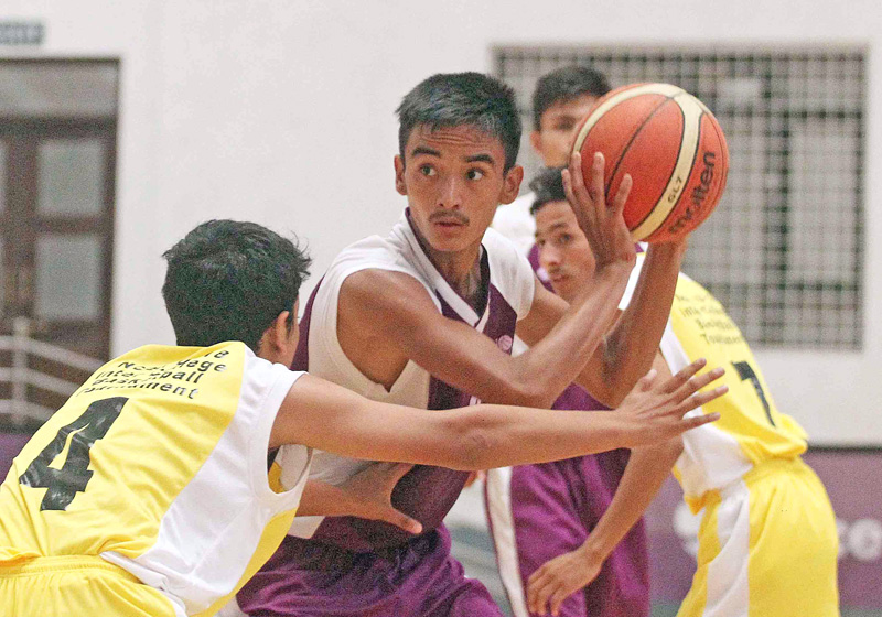 Shashi Parajuli of Prime College tries to beat past Bibek Niraula (left) of Times International College during their Ncell U-18 Inter-college Basketball Tournament at the Nepali Army Sports Complex in Lalitpur on Monday. Photo:  Udipt Singh Chhetry/THT