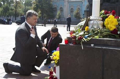 Ukraine's President Petro Poroshenko, left, and parliament speaker Volodymyr Groisman lay flowers by the photo of a police officer who was killed in a Monday clash, in front of Parliament in Kiev, Ukraine, Tuesday, Sept. 1, 2015. AP