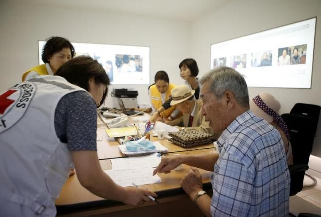 A South Korean man (R) who said he has family members living in North Korea, gets help to prepare a document for reunion, at the administration office for separated families in the Red Cross building, in Seoul, South Korea, September 7, 2015. REUTERS/Kim Hong-Ji