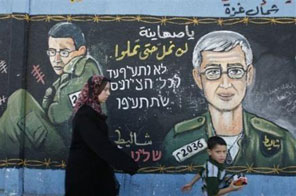 Palestinians walk past a mural dedicated to Gilad Shalit Source: AFP