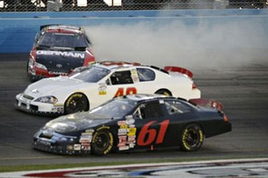 Michael Annett, top, skids out of turn one as Josh Wise (61) and Scott Lagasse Jr. drive past during the 15th lap of the NASCAR Nationwide Bashas' Supermarket 200 auto race Friday, April 9, 2010 in Avondale, Ariz.    Source: AFP