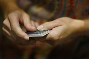 A US woman prepares to cut up her credit cards in a bid to dig herself out of credit card debt during a religious sermon in Kendall, Florida. The US Federal Reserve has held rock-bottom interest rates for
