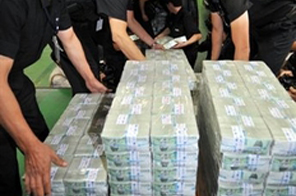 Security workers unload new money at the country's central bank in Seoul. The financial body Friday froze its key interest rate at a record low 2.0 percent for the eighth straight month to nurture a nascent economic recovery. Source: AFP