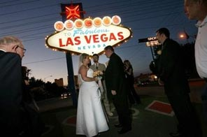 A couple is pictured getting married under the famous 'Welcome to Fabulous Las Vegas sign' surrounded by family and friends. Source: AFP