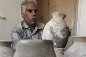 In this photo taken Monday, June 22, 2009, a worker of the Palestinian ministry of Tourism looks at pieces of pottery that were from the early Bronze age and were found recently in the West Bank town of Bethlehem.  Source: AP