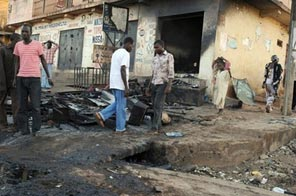 People walk past a shop that was burnt during unrest in Jos, Nigeria, in 2008. Source: AFP