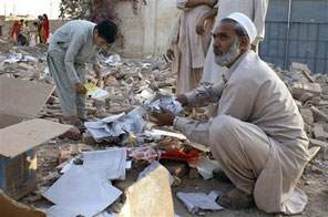 A man collects torn books at the site of a damaged girls high school, wrecked by suspected militants on early morning on Sunday, Nov. 1, 2009 in Karigar Garhi village near Bara, the main town of Pakistan's troubled tribal region Khyber along Afghan border. Militants are targeting mostly girls schools as they are against females' education. Source: AP