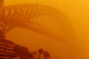 The Sydney Harbour Bridge is shrouded in an eerie blanket of dust on September 23, 2009. Sydney's cars and buildings turned orange as strong winds blew desert dust across the city, snarling commuter and air transport and prompting a warning for children and the elderly to stay indoors. Source: AFP