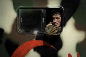 An Afghan army medic soldier looks out from an ambulance in Kabul. Seven members of the Afghan security forces were killed in a NATO air strike in remote western Afghanistan, the defence ministry has said. Source: AFP/Nicolas Asfouri