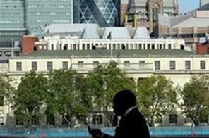File photo shows a man passing in front of the skyline of the main financial district of London. Source: AFP