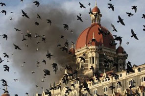 Smoke is seen coming from the Taj Mahal Hotel in Mumbai on November 27, 2008. Italian police have arrested two Pakistanis whose money transfer service was allegedly used by those in contact with militants who carried out the 2008 Mumbai attacks, media have reported. Source: AFP