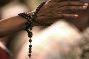 A Rosary hangs from a church-goer's wrist during mass in a Miami church. In what is being described as a miracle, an elderly woman has been pulled alive and singing from the rubble of Haiti's Roman Catholic cathedral, one full week after a killer quake tore the building to the ground. Source: AFP