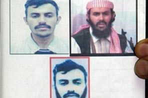 A jounalist holds up a Yemeni interior ministry document, marked on top in red 'wanted criminal', and showing three different undated pictures of a suspected military chief of al-Qaeda network in Yemen, identified as Qassem al-Rimi. Source: AFP