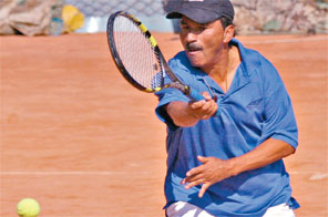 Kamal Thapa returns to Gauri Shankar Shrestha in the above 35-yrs veteran singles match during the second APF Open Lawn Tennis Tournament in Kathmandu on Wednesday. Source: THT