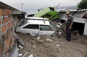 A man looks at cars damaged in a landslide east of San Salvador on November 8. A late-season storm has ravaged parts of Central America as floods and landslides killed at least 124 in El Salvador, where the president declared a state of emergency, and thousands were left homeless in Nicaragua. Source: AFP