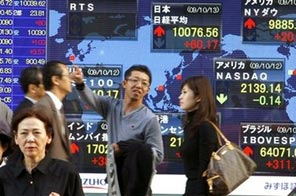 People walk past an electronic stock indicator in central Tokyo, Japan, Tuesday, Oct. 13, 2009. Japan's benchmark Nikkei stock average Source: AP