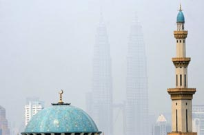 Malaysia's landmark Petronas Twin Towers are seen in the background behind the minerat of a mosque in Kuala Lumpur.  Source: AFP
