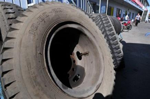 A woman walks by a rack of tyres at a bus depot in Beijing Source: AFP