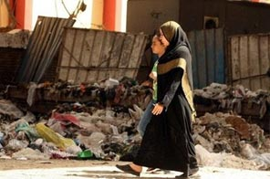 Egyptian women walk past accumulated garbage in Cairo. In their overcrowded areas, overflowing with litter, many Egyptians have trouble coming to grips with the dramatic measures taken by authorities to combat the A(H1N1) flu. Source: AFP