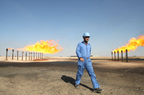 A picture taken on February 3, 2009 shows an engineer walking past the chimneys at the Barjisiya oil field in Zubair One, southwest of the southern Iraqi city of Basra, 550 kms from Baghdad. Iraq will unveil which foreign firms have won contracts to develop its oil and gas fields, nearly four decades after Saddam Hussein nationalised the country's energy infrastructure. The deals, likely to be on June 29 and 30, will provide the government with much-needed revenue as it struggles to rebuild the country after three wars and 20 years of debilitating economic sanctions. Source: AFP