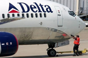 A Delta Airlines ground crew employee finishes the push-back of an outbound flight. Delta Air Lines said it plans to slash flight capacity by 10 percent in 2009 in the face of the global recession and rising fuel prices. Source: AFP