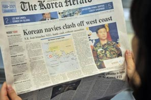 A S.Korean woman reads a newspaper reporting the clash of North and South Korean navies, in Seoul. A N.Korean patrol boat was set ablaze after exchanging fire with South's navy on November 10. Source: AFP