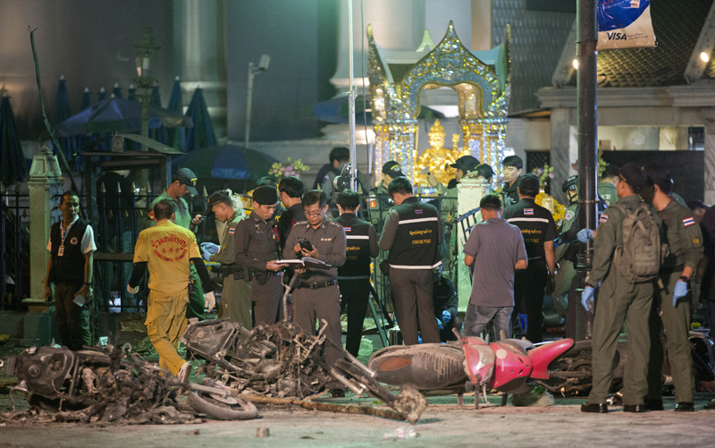 FILE - In this Aug. 17, 2015 file photo, police investigate the scene at the Erawan Shrine after an explosion in Bangkok. Police in Thailand said Saturday, Sept. 26, 2015, they have gathered enough evidence to prosecute two arrested men whom they accuse of carrying out Augustu2019s deadly Bangkok bombing.(AP Photo/Mark Baker, File)
