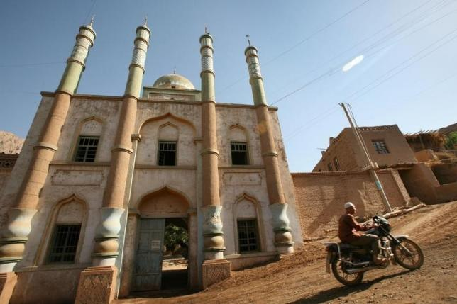 A man rides his motorcycle in front of a mosque at a village near the city of Turpan in China's remote far western region of Xinjiang, May 20, 2006. REUTERS/Reinhard Krause/Files