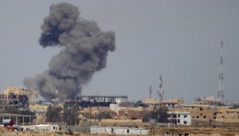 A plume of smoke rises above a building during an air strike in Tikrit March 27, 2015. Photo: Reuters