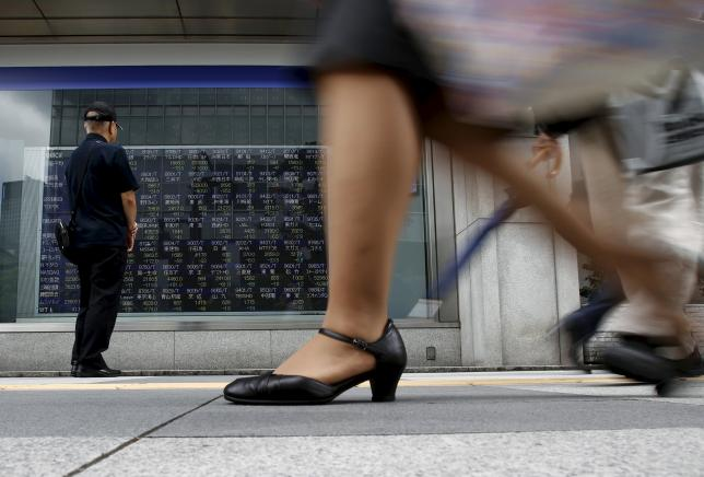 A pedestrian stops to look at an electronic board showing the various stock prices outside a brokerage in Tokyo, Japan, August 21, 2015. REUTERS/Yuya Shino