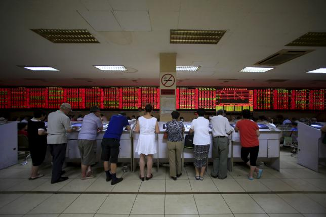 Investors look at computer screens in front of an electronic board showing stock information at a brokerage house in Shanghai, China, September 7, 2015.  REUTERS/Aly Song