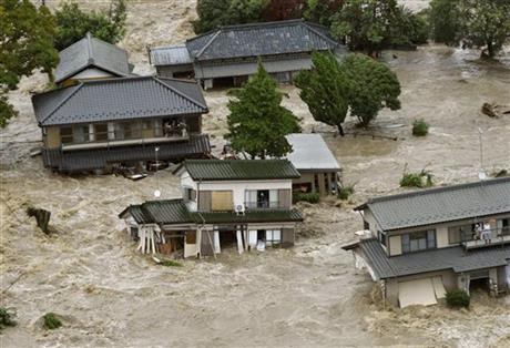 People inside houses wait to be rescued as the houses are submerged in water flooded from a river in Joso, Ibaraki prefecture, northeast of Tokyo Thursday, Sept. 10, 2015. AP