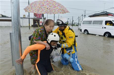 Police officers help a woman to evacuate through a flooded street in Joso, Ibaraki prefecture, northeast of Tokyo Thursday, Sept. 10, 2015. Photo: Reuters