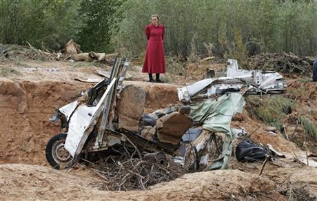 A woman looks at a damaged vehicle swept away during a flash flood Tuesday, Sept. 15, 2015, in Hildale, Utah. AP