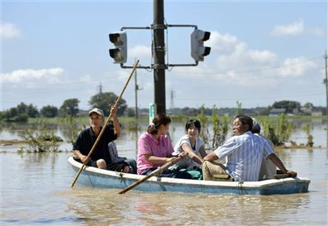 Residents paddle a boat past a traffic light in the flooded road in Joso, Ibaraki prefecture, northeast of Tokyo, Friday, Sept. 11, 2015. AP