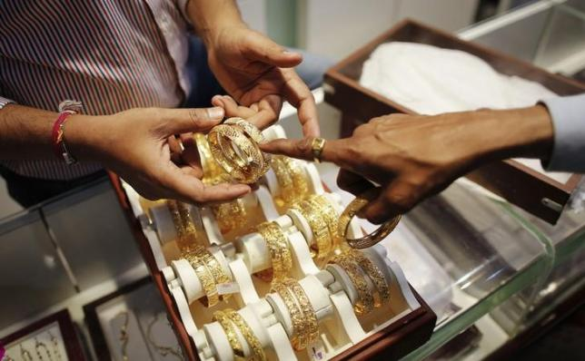 An employee shows gold bangles to a customer at a jewellery showroom on the occasion of Dhanteras, a Hindu festival associated with Lakshmi, the goddess of wealth, at a market in Mumbai November 1, 2013.  REUTERS/Danish Siddiqui