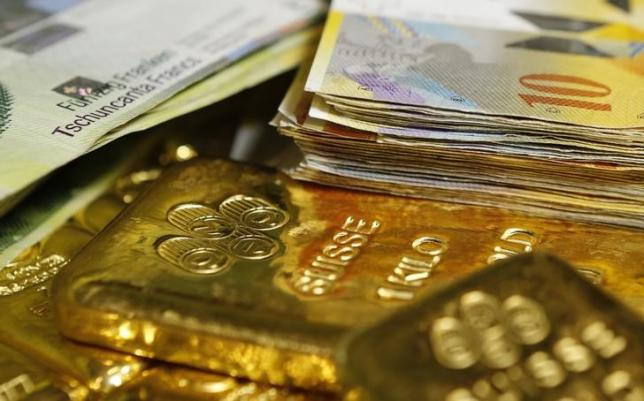 Gold bars and Swiss Franc banknotes are seen in this illustration picture taken at the GSA in Vienna November 13, 2014. REUTERS/Leonhard Foeger/Files