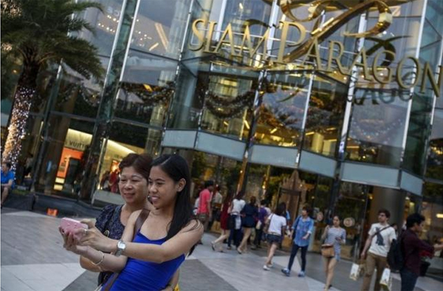 Tourists take a photo of themselves in front of Siam Paragon Department Store in central Bangkok December 16, 2013. Photo Reuters