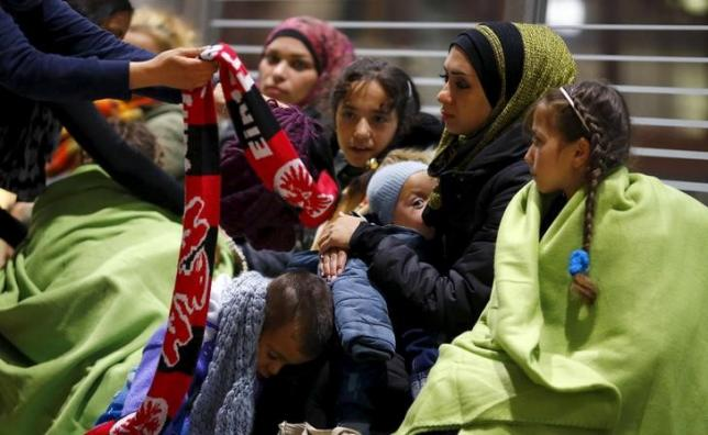 Wellwishers offer warm clothing to Syrians after they arrived on a train from Budapest's Keleti station at the railway station of the airport in Frankfurt, Germany, early morning September 6, 2015. REUTERS/Kai Pfaffenbach