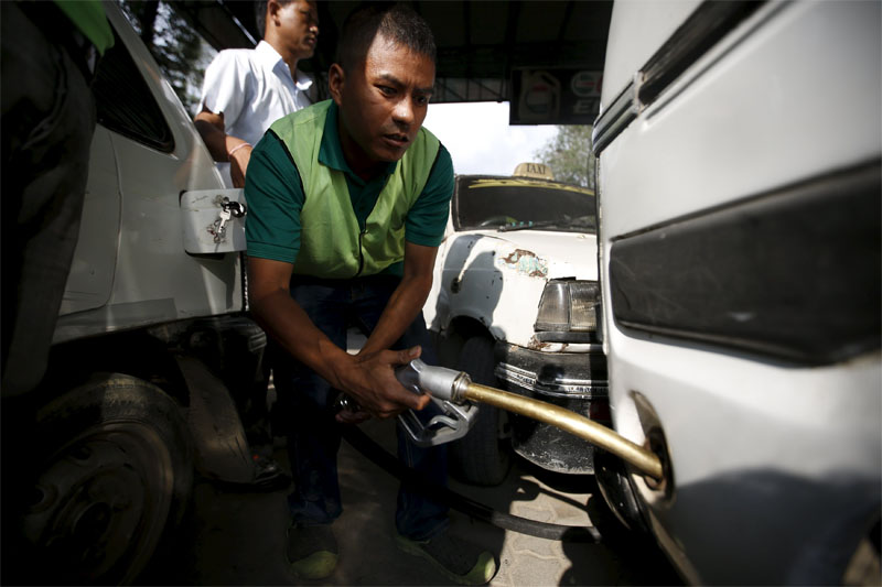 A worker refills petrol on a vehicle at a fuel station in Kathmandu in September 28, 2015. Photo: Reuters/File