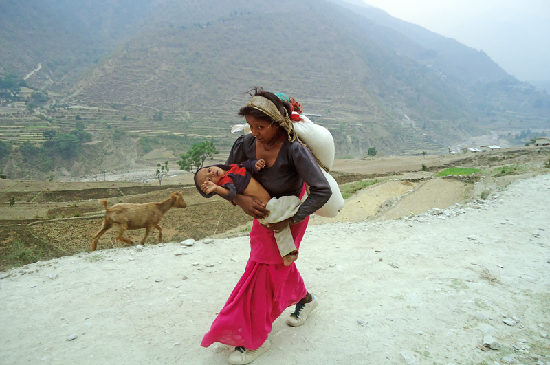 A woman travelling with a sack of rice on her back and with her child in her bosom from Kolti branch of Nepal Food Corporation to her house in Wai VDC on Sunday. Photo: THT