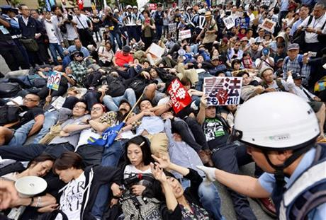 Protesters lie down arm in arm together as a police officer tries to clear them in front of the venue hotel for a public hearing on the security legislation in Yokohama, south of Tokyo, Wednesday, Sept. 16, 2015. AP