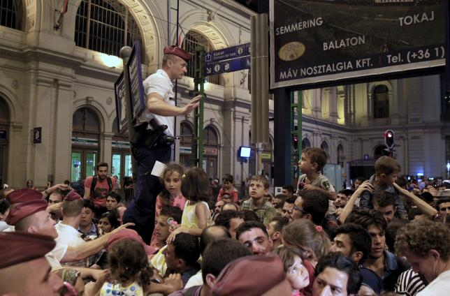 A policeman tries to control migrants as ticket control rules now mandate each passenger to have allocated seats on trains bound for the West from Budapest, Hungary, on August 31, 2015.  Photo: REUTERS