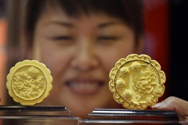 A saleswoman displays gold mooncake sculptures at a shop in Taiyuan, Shanxi province, September 10, 2013. Photo: REUTERS