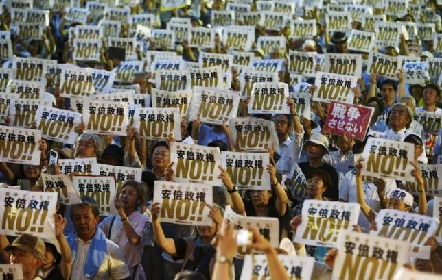 People hold placards denouncing Japan's Prime Minister Shinzo Abe's security-related legislation during an anti-government rally in Tokyo July 24, 2015. REUTERS/Thomas Peter